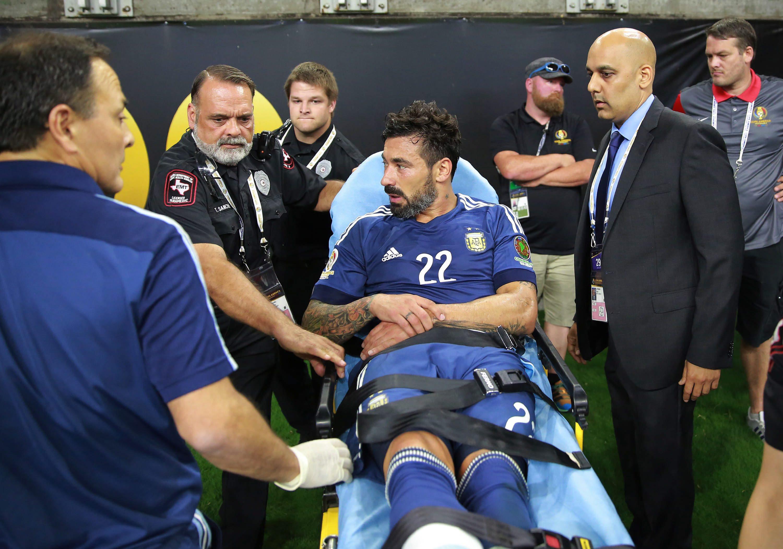 RJC10. HOUSTON (EE.UU.), 21/06/2016.- El jugador de Argentina Ezequiel Lavezzi (c) recibe atención después de chocar contra una valla de publicidad hoy, martes 21 de junio de 2016, durante un partido entre Argentina y EE.UU. en los cuartos de final de la Copa América Centenario en el estadio NRG en Houston (EE.UU.). EFE/RICHARD CARSON